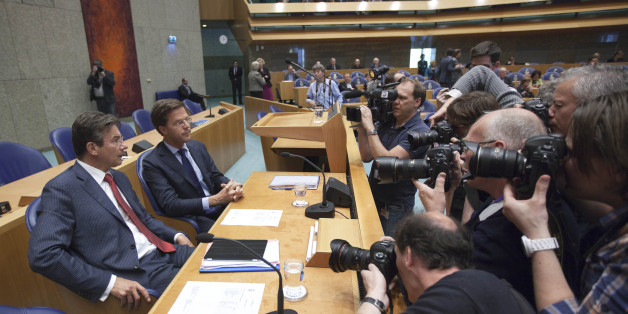 Photographers and cameramen crowd around caretaker Prime Minister Mark Rutte, second left, and deputy prime minister Maxime Verhagen, left, in parliament in The Hague, Netherlands, Tuesday April 24, 2012. Rutte appealed to a polarized Dutch Parliament on Tuesday to help him get the economy back on track rather than let the country drift in political limbo until new elections. Speaking publicly for the first time since he tendered his resignation Monday, Rutte said the nation, long considered one of Europe's most fiscally responsible, has no time to waste in tackling its economic woes. (AP Photo/Peter Dejong)