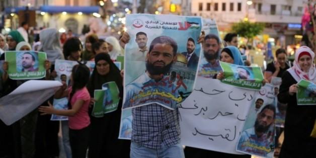 Des manifestants brandissent des affiches avec le portrait de l'avocat Mohammed Allan