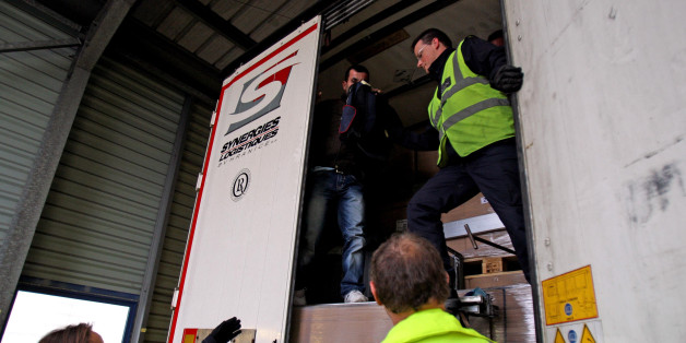 A stowaway passenger climbs down from a lorry trailer helped by UK Border Control after being discovered hiding behind boxes in the back of the trailer at Calais Ferry Port in France.