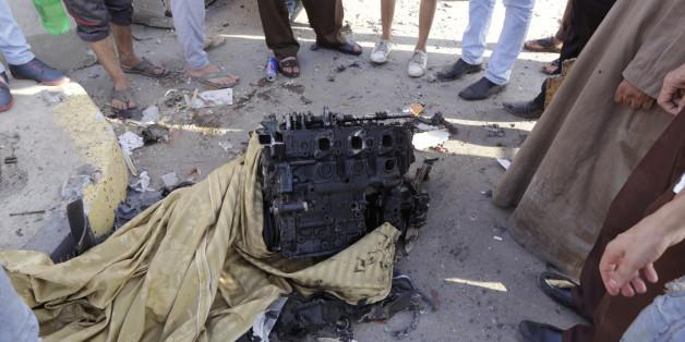 Des Egyptiens devant le moteur du véhicule utilisé dans un attentat visant le bâtiment de la sécurité nationale le jeudi 20 août 2015, dans le quartier de Shubra El Kheima au Caire