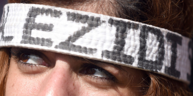 A demonstrator wears a headband reading Yazidis , in Hannover, Germany,  Saturday Aug. 16, 2014.  Thousands of people in Germany have protested against the persecution of the Yazidi minority in Iraq. Police say at least 10,000 people attended the biggest demonstration in the north German city of Hannover on Saturday. Protesters carried banners demanding that the international community protect the Yazidi people and other minorities from the Islamist State extremist group. (AP Photo/dpa,Swen Pfoertner)