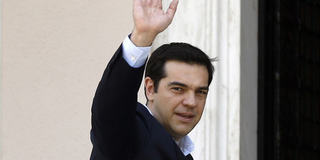Greece's Prime Minister Alexis Tsipras waves to the media as he arrives at Maximos Mansion after a swearing in ceremony of his new ministers in Athens, Saturday, July 18, 2015. Tsipras reshuffled his Cabinet on Friday following a rebellion within his party over a parliamentary vote to approve the measures demanded for the bailout talks to start. Greek parliament approved creditor's demand for austerity measures. (AP Photo/Thanassis Stavrakis)