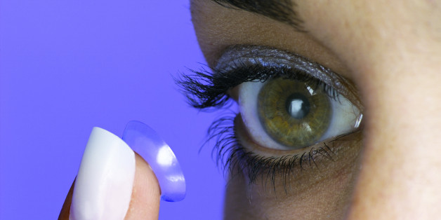 Photo, woman putting a contact lens in her eye, eye only, close-up, Color, Low res