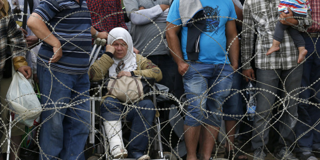 Migrants stand behind the barbed wire set by Macedonian police to stop thousands of migrants entering Macedonia illegally from Greece near the southern Macedonian town of Gevgelija, Saturday, Aug. 22, 2015. About 39,000 people, mostly Syrian migrants, have been registered as passing through Macedonia in the past month, twice as many as the month before.  (AP Photo/Darko Vojinovic)