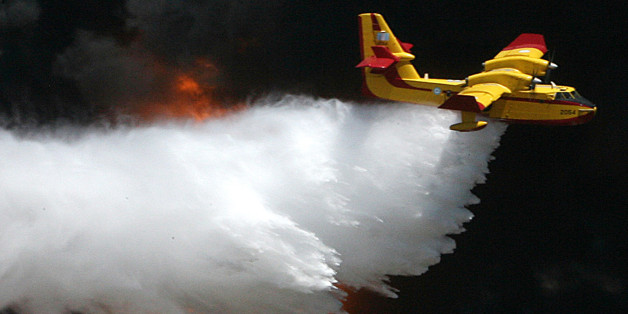 ** FILE **  A Greek Airforces Canadair CL-415 firefighting plane dumps water on flames at a solvent factory at the port of Lavrio, southeast of Athens, in this Wednesday, July 26, 2006 file photo. A similar type of plane crashed while battling a forest fire on the Greek island of Evia on Monday, July 23, 2007. Both crew members were killed when the plane slammed into a hillside amid thick clouds of smoke. Five firefighters and two civilians have died in fires in Greece this summer. (AP Photo/Kostas Tsironis)