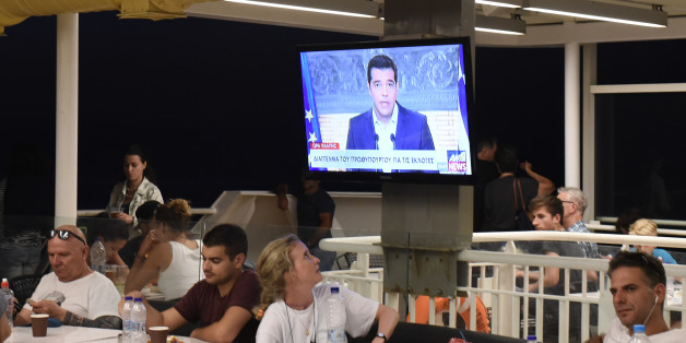 Greek Prime Minister Alexis Tsipras, on a screen during a televised address to the nation, as a tourist watches on a ferry traveling in the Aegean sea, near Syros island, Greece, Thursday, Aug. 20, 2015. Tsipras announced his government's resignation and called early elections Thursday, seeking to consolidate his mandate to implement a new three-year international bailout that sparked a rebellion within his radical left Syriza party. (AP Photo/Giannis Papanikos)