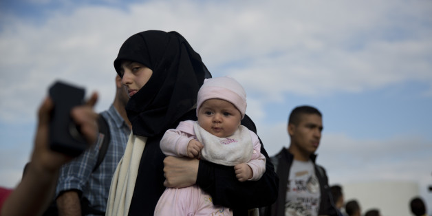 A Syrian refugee holds a baby after they arrived from eastern islands with a ferry at Athens' port of Piraeus, on Sunday, Aug. 23, 2015. Greece has been overwhelmed this year by record numbers of migrants. (AP Photo/Petros Giannakouris)