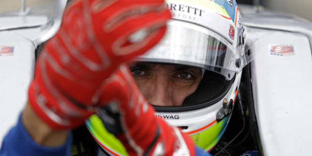 Justin Wilson, of England, dons his gloves as he prepares to drive during practice for the Indianapolis 500 auto race at Indianapolis Motor Speedway in Indianapolis, Thursday, May 14, 2015.  (AP Photo/Michael Conroy)
