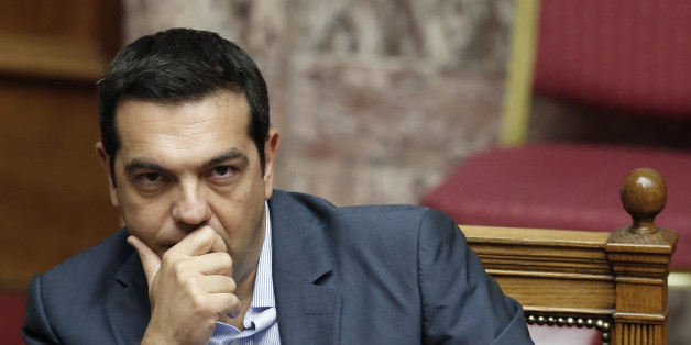 Greek Prime Minister Alexis Tsipras liestens during a parliamentary session in Athens, Friday, Aug. 14, 2015. Greek lawmakers are continuing a debate in parliament to approve a massive new bailout deal after repeated delays over procedure and dissent within the governing left-wing Syriza party caused the session to last through the night. (AP Photo/Yannis Liakos)