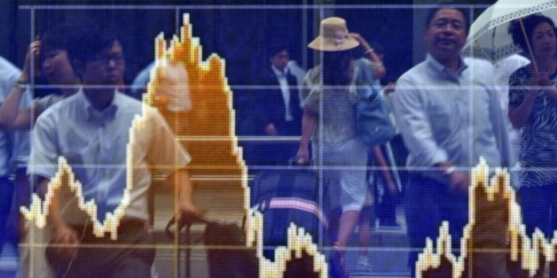 Des piétons se reflètent sur un écran de cotation à Tokyo le 24 août 2015
