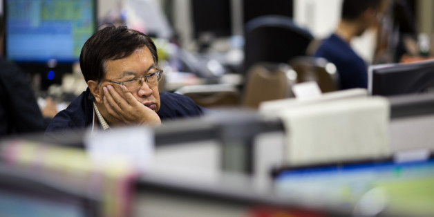 A stockbroker sits in front of a screen displaying share prices at a securities brokerage in Hong Kong, China, on Monday, Aug. 24, 2015. Hong Kong's snowballing stock losses are, by one measure, the most extreme since the crash of 1987. Photographer: Jerome Favre/Bloomberg via Getty Images