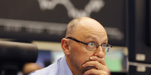 A trader watches his screens when the curve of the German stock index DAX fell under 10,000 points at the stock market in Frankfurt, Germany, Monday, Aug. 24, 2015. (AP Photo/Michael Probst)