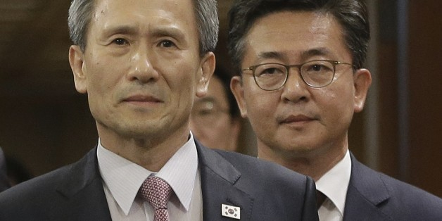 South Korean presidential security adviser Kim Kwan-jin, left, and Unification Minister Hong Yong-pyo arrive to hold a press conference at the presidential house in Seoul, South Korea, Tuesday, Aug. 25, 2015. South Korea has agreed to halt propaganda broadcasts at noon Tuesday after North Korea expressed regret over a recent land mine blast that maimed two South Korean troops, both Koreas announced after three days of intense talks aimed at defusing soaring tension between the rivals.(AP Photo/A
