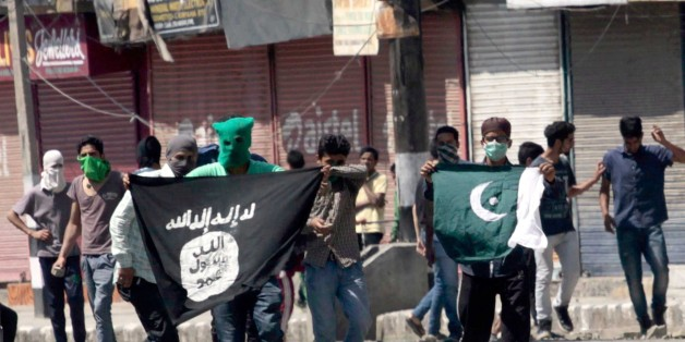 SRINAGAR, INDIA - JUNE 27: Kashmiri protesters displaying the flags of ISIS and Pakistan during a protest against alleged desecration of Jamia Masjid by police personnel yesterday after Friday prayers, on June 27, 2015 in Srinagar, India. Clashes broke out in several parts of downtown Srinagar on Saturday against the alleged desecration of Jamia Masjid by government forces yesterday. Reacting very sharply against police action, Auqaf Jamia Masjid, which functions under Mirwaiz, called for a shut