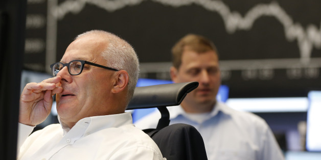 A trader wipes his nose when the curve of the German stock index DAX fell under 10,000 points at the stock market in Frankfurt, Germany, Monday, Aug. 24, 2015. (AP Photo/Michael Probst)