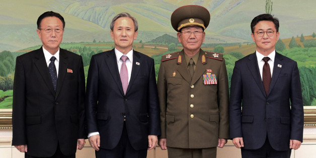 In this photo provided by the South Korean Unification Ministry, South Korean Unification Minister Hong Yong-pyo, right, and presidential security adviser Kim Kwan-jin, second from left,  pose with Kim Yang Gon, right, a senior North Korean official responsible for South Korean affairs, and Hwang Pyong So, North Korea' top political officer for the Korean People's Army, after their meeting at the border village of Panmunjom in Paju, South Korea, Tuesday, Aug. 25, 2015. South Korea has agreed to