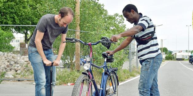 """- Tobias Fleiter (l) von der Initiative """"bikes without borders"""" pumpt in in Karlsruhe mit Flüchtling Tairou Nasif aus Togo den Reifen eines Fahrrads auf"""