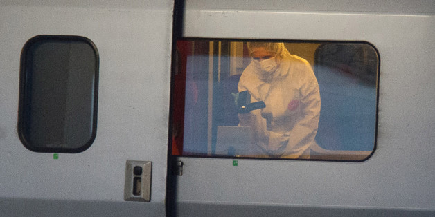 ALTERNATE CROP TO REB103 - A police officer videos the crime scene inside a Thalys train at Arras train station, northern France, Friday, Aug. 21, 2015. A gunman opened fire with an automatic weapon on a high-speed train traveling from Amsterdam to Paris Friday, wounding three people before being subdued by two American passengers, officials said. French Interior Minister Bernard Cazeneuve, speaking in Arras in northern France where the suspected was detained, said one of the Americans was hospi