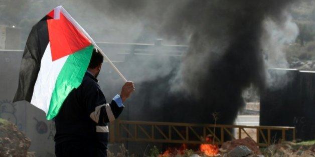 Un manifestant palestinien brandit le drapeau national et regarde des pneus bruler près de la barrière de séparation israélienne, le 14 janvier 2011, dans le village de Nilin à l'ouest de Ramallah