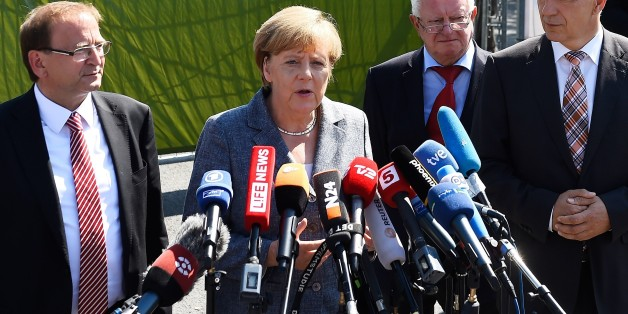 German Chancellor Angela Merkel (2nd L) makes a statement flanked by Heidenau's mayor Juergen Opitz (L), Red Cross president Rudolf Seiters (2nd R) and Saxony's State Premier Stanislaw Tillich (R) after a visit to a shelter for asylum-seekers in Heidenau, eastern Germany