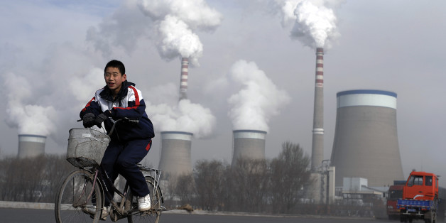 A Chinese boy cycles past a cooling towers of a coal-fired power plant in Dadong, Shanxi province, China, Thursday, Dec. 3, 2009. The U.N.'s environment chief said Tuesday he is optimistic that the climate change talks beginning in Copenhagen next week will reach a deal setting firm targets to cut carbon emissions. (AP Photo/Andy Wong)