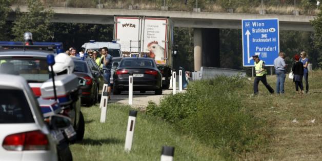 Des policiers autour du camion abandonné sur la bande d'arrêt d'urgence d'une autoroute dans lequel des corps en décomposition ont été découverts le 27 août 2015 près de Neusiedl am See en Autriche