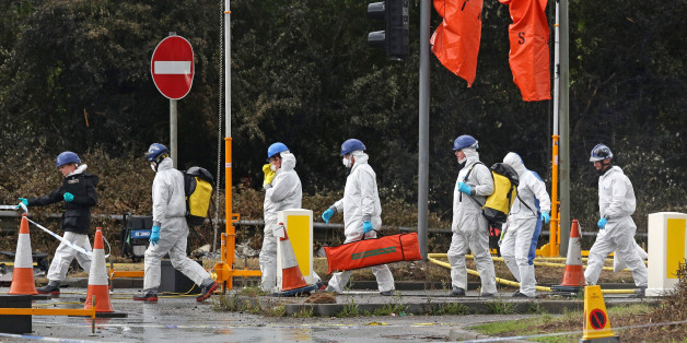 SHOREHAM, ENGLAND - AUGUST 24: Emergency service workers in protective overalls walk on the A27 road near where a Hawker Hunter fighter jet crashed during on August 24, 2015 in Shoreham, England. The aircraft came down while performing at the Shoreham Airshow on August 22nd. Police now expect the death toll to rise to as many as 20 victims.  (Photo by Peter Macdiarmid/Getty Images)