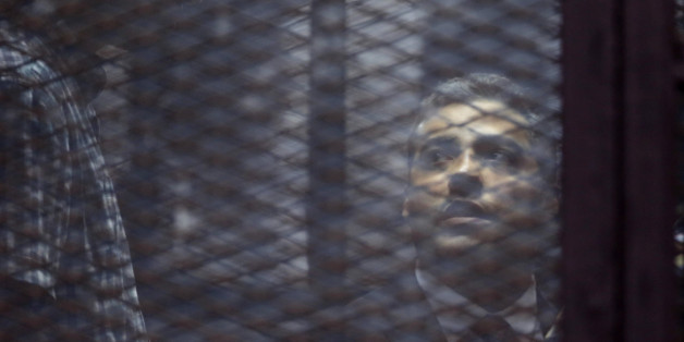 Canadian Al-Jazeera English journalist Mohammed Fahmy, listens to his verdict in a soundproof glass cage inside a makeshift courtroom in Tora prison in Cairo, Egypt, Saturday, Aug. 29, 2015. An Egyptian court on Saturday sentenced three Al-Jazeera English journalists, including Fahmy, to three years in prison, the last twist in a long-running trial criticized worldwide by press freedom advocates and human rights activists. (AP Photo/Amr Nabil)