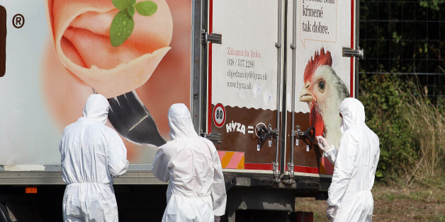 Investigators stand near a  truck that  stands on the shoulder of the highway A4 near Parndorf south of Vienna, Austria, Thursday, Aug 27, 2015. At least 20 migrants were found dead in the truck parked on the Austrian highway leading from the Hungarian border, police said. (AP Photo/Ronald Zak)