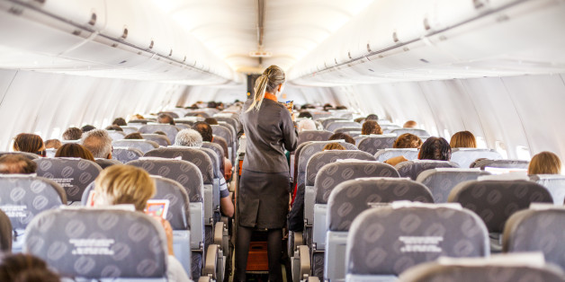 A scene from the inside of a airplane with passengers and attendants working.