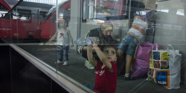 Des enfants syriens et leurs parents attendent un train pour l'Allemagne, dans la gare de Vienne en Autriche le 31 août 2015
