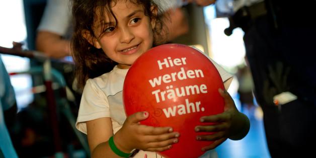 Ein kleines Mädchen aus Syrien hält am 31.08.2015 in München einen Luftballon fest