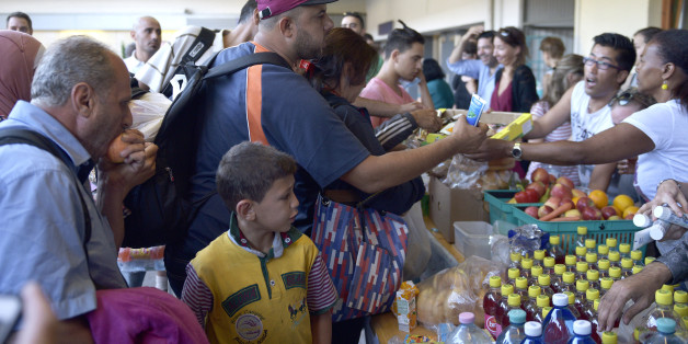 People receive food after they  arrived at a  railway station in Vienna, Austria, on Tuesday, Sept. 1, 2015. Some hundreds of migrants arrived by train from southern Europe, after making a perilous journey into Europe. (AP Photo/Hans Punz)