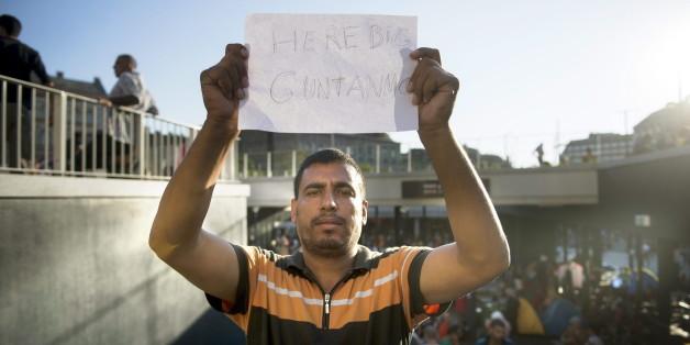 Ein Flüchtling in Budapest hält eine Papier hoch, auf dem er das Lager mit Guantanamo vergleicht
