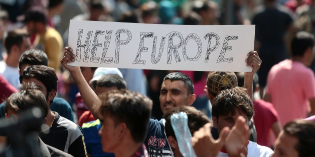 A man hold a placard reading 'Help Europe' as Syrian and Afgan refugees attend a protest rally to demand to travel to Germany on September 2, 2015 outside the Keleti (East) railway station in Budapest. Hungarian authorities face mounting anger from thousands of migrants who are unable to board trains to western European countries after the main Budapest station was closed. AFP PHOTO / FERENC ISZA        (Photo credit should read FERENC ISZA/AFP/Getty Images)