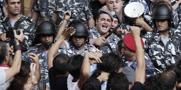 Lebanese anti-government protesters clashes with policemen outside the Environment Ministry in support of activists staging a sit-in inside, in downtown Beirut, Lebanon, Tuesday, Sept. 1, 2015. Lebanese security forces dragged a number of activists out of the Environment Ministry in downtown Beirut, where they were staging an hours-long sit-in on Tuesday demanding the minister's resignation over a trash crisis that has ignited mass protests. (AP Photo/Bilal Hussein)