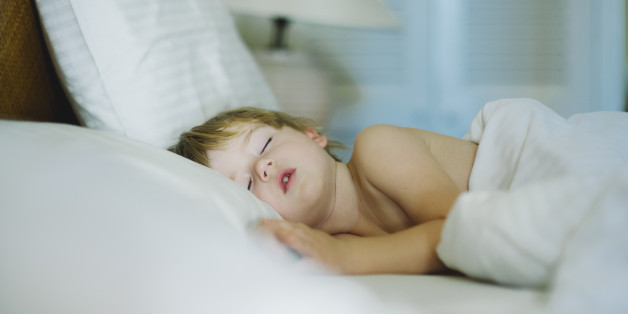 Young sleeping boy in a hotel room.