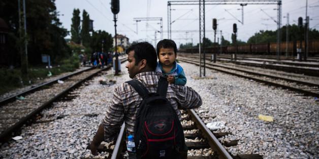 Un migrant et son fils sur la route de Gevgelija, une ville à la frontière de la Grèce et de la Macédoine, le 3 août