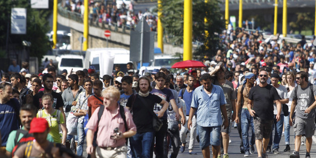 Migrants walk along the Hegyalja Street in Budapest, Hungary, Friday, Sept. 4, 2015. Several thousand migrants left the Keleti railway station in Budapest this afternoon heading for Germany on foot. (Zsolt Szigetvary/MTI via AP) )