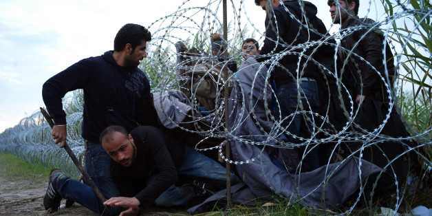 FILE - In this Aug. 26, 2015, file photo, Syrian refugees cross into Hungary underneath the border fence on the Hungarian - Serbian border near Roszke, Hungary. From the three-year-old boy who washed ashore on a Turkish beach to the 71 migrants who suffocated in a truck in Austria to the daily scenes of chaos unfolding in European cities as governments try to halt a human tide heading north. There is no let up to the horrors that Syria's civil war keeps producing. Syria's brutal confli