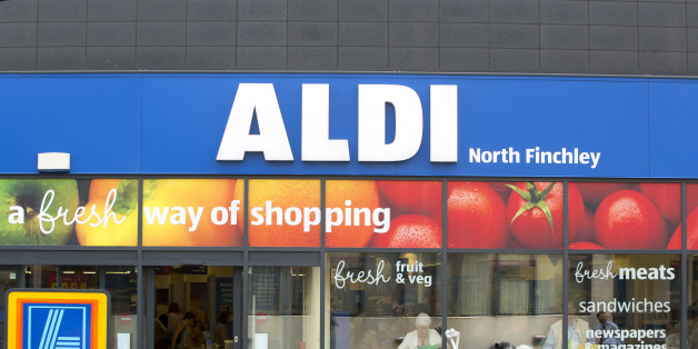 A woman using a motorized cart, sits outside the entrance to an Aldi supermarket store in London, U.K., on Monday, June 29, 2015. The growth of Aldi and fellow German-owned discounter Lidl has changed the British grocery landscape over the last five years. Photographer: Jason Alden/Bloomberg via Getty Images