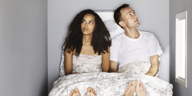 young couple in small bed room, sitting in bed looking confused