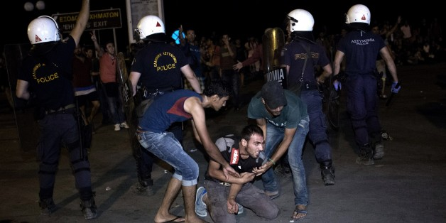 Migrants help another one to stand up during clashes with Greek police, while migrants try to board a ferry boat, in the port of Mytilene on the Greek Aegean island of Lesbos on September 5, 2015. More than 230,000 refugees and migrants arrived in Greece by sea this year, a huge rise from 17,500 in the same period in 2014, deputy shipping minister Nikos Zois said on September 3. AFP PHOTO / ANGELOS TZORTZINIS        (Photo credit should read ANGELOS TZORTZINIS/AFP/Getty Images)