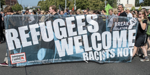 Protesters demonstrate with a banner 'Refugees welcome!' in Dresden, eastern Germany, Saturday, Aug. 29, 2015. A refugee shelter was attacked by far-right protesters in Heidenau near Dresden over the last weekend. (AP Photo/Jens Meyer)