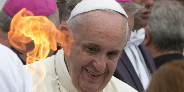 Pope Francis looks at a torch held by a Paralympic athlete, during his weekly general audience in St. Peter's Square at the Vatican, Wednesday, Sept. 2, 2015. (AP Photo/Alessandra Tarantino)