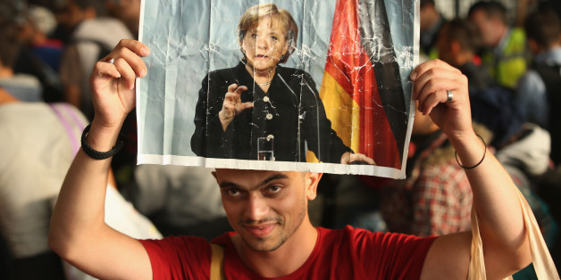 Ein Flüchtling hält ein Bild von Kanzlerin Angela Merkel hoch