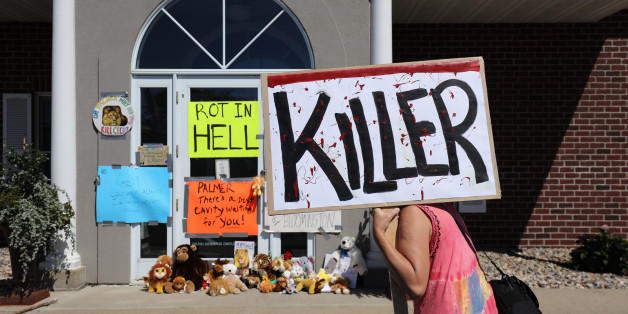 BLOOMINGTON, MN - JULY 29:  Protesters call attention to the alleged poaching of Cecil the lion, in the parking lot of Dr. Walter Palmer's River Bluff Dental Clinic on July 29, 2015 in Bloomington, Minnesota. According to reports, the 13-year-old lion was lured out of a national park in Zimbabwe and killed by Dr. Palmer, who had paid at least $50,000 for the hunt. (Photo by Adam Bettcher/Getty Images)