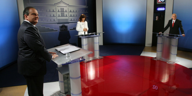 Greek Prime Minister Costas Karamanlis, left, and Greece's opposition Socialists leader George Papandreou, far right, look on as a Greek television journalist Maria Houkli checks her papers before a debate in Athens on Tuesday, Sept. 22, 2009. Greece's opposition Socialists have retained a strong lead in the last opinion polls published before the Oct. 4 general election. Three nationwide surveys published in newspapers Friday give George Papandreou's Socialists a lead of between 6 and 7 points over Prime Minister Costas Karamanlis' conservatives all projecting the main opposition party will win enough seats in parliament to form the next government. (AP Photo/Thanassis Stavrakis)