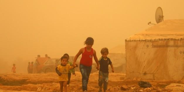 Des enfants syriens dans un camp de réfugiés près de Baalbeck, lors d'une tempête de sable le 7 septembre 2015 au Liban