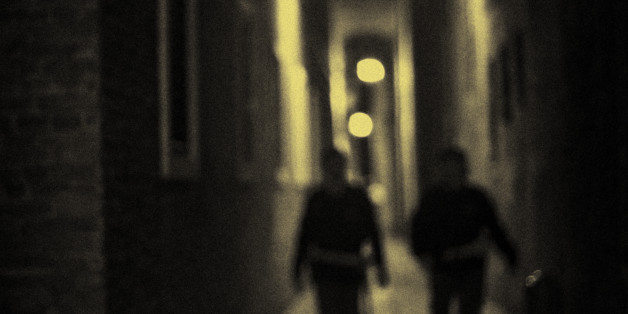 At night, a couple of police officers walk down the Calle Albanesi in Venice, Italy.